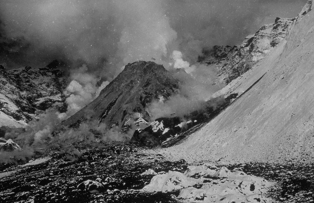 By the time of this 27 August 1956 photo, a new lava dome growing in the Bezymianny crater had reached a height of 320 m. The dome began growing in April, following a catastrophic eruption on 30 March in which the summit of the volcano collapsed, producing a massive debris avalanche and lateral blast towards the SE. The walls of the resulting horseshoe-shaped crater 1.3 x 2.8 km and 700 m deep that can be seen behind the lava dome. Gas emissions rise from the summit and base of the dome.  Photo by G.S. Gorshkov, 1956 (Institute of Volcanology, Petropavlovsk, published in Green and Short, 1971).