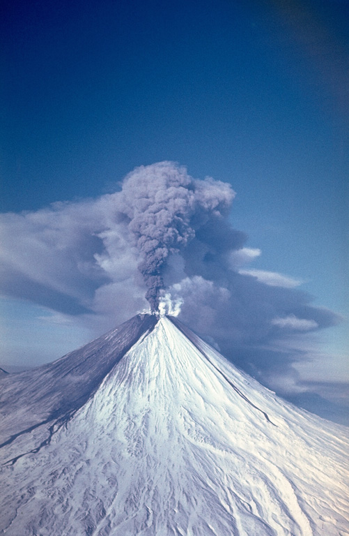 An ash plume erupting from the summit crater of Kamchatka's Kliuchevskoy volcano on 9 February 1987, traveling to the west. Ashfall from earlier eruptions darkens the southern flank of the volcano and several lahar deposits are visible. Explosive eruptions from the summit crater during 1986-1990 were accompanied by lava flows from both summit and flank vents. Photo by Alexander Belousov, 1987 (Institute of Volcanology, Petropavlovsk).