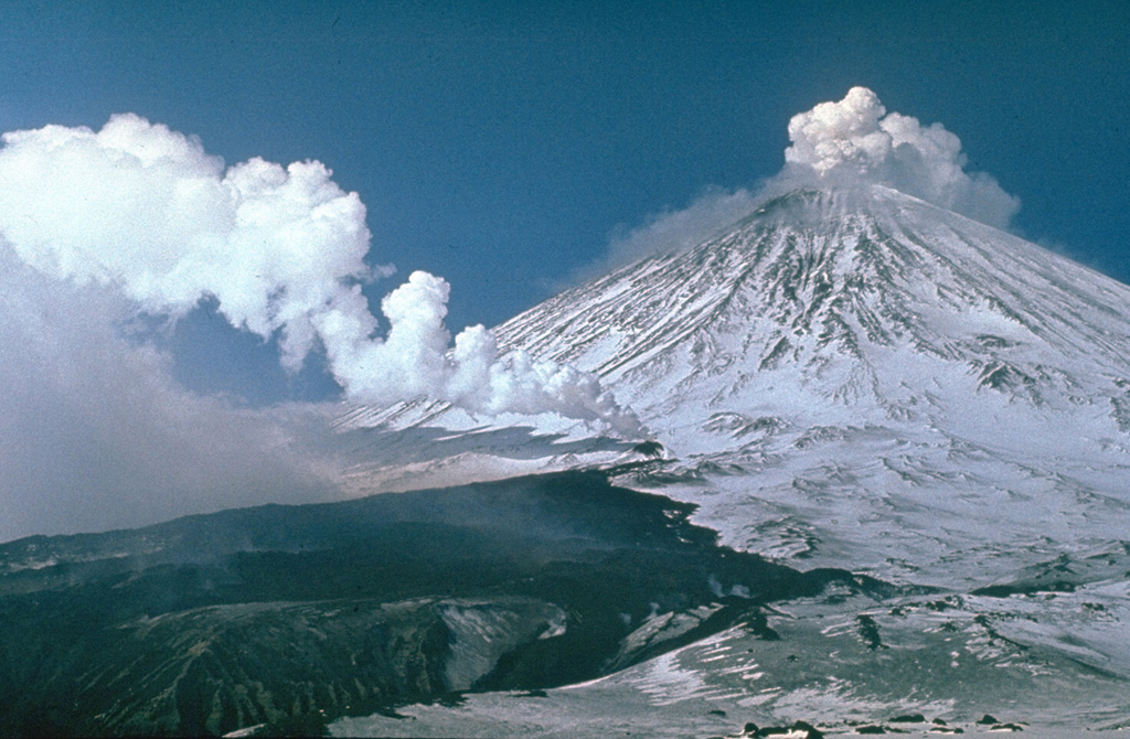 Gas-and-steam plume emissions occurred simultaneously from vents on the SW flank and the summit of Klyuchevskoy volcano in 1983. The SW-flank vent within a 200-m-long fissure produced the dark lava flow that melted the glacier surface, providing a channel for the lava flow and producing lahars that traveled 15 km. The flank eruption began on 8 March and was initially was restricted to a glacier gorge, but then bifurcated, forming a small lava field. Intermittent summit crater explosive activity had been occurring since October 1982. Photo by Yuri Doubik, 1983 (Institute of Volcanology, Petropavlovsk).