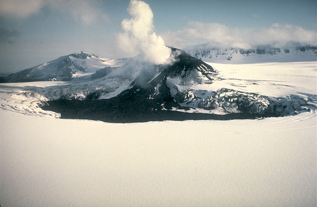 A scoria cone on the western floor of the summit caldera of Veniaminof was the source of the dark lava flow that melted through the glacial icecap. This photo was taken from the SE on 15 June 1984, two months after the eruption ended, and shows the rim of the 8 x 11 km wide caldera in the background. The caldera rim contains Cone Glacier on the west side (to the extreme left) and is completely overtopped by glaciers on the south and SE sides. Veniaminof is one of the most voluminous and most active volcanoes on the Alaska Peninsula. Photo by Alaska Volcano Observatory, U.S. Geological Survey, 1984.