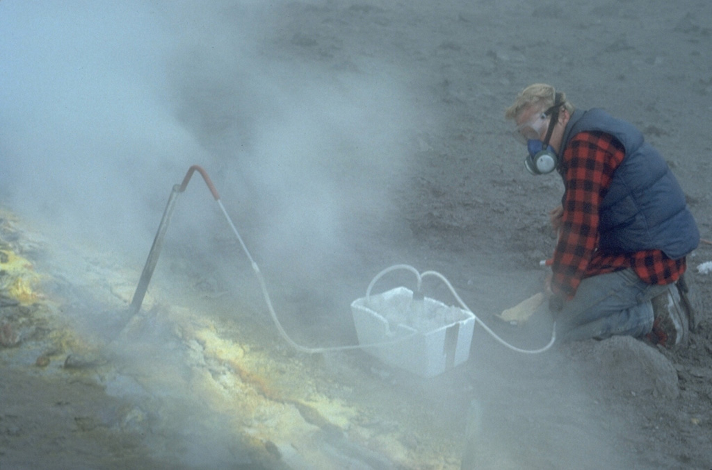 Volcanologist Bob Symonds takes gas samples from a sulfur-encrusted fumarole at the summit of Augustine during a quiescent period of the 1986 eruption. Fumarole condensates had a pH of between 0 and 0.5. The maximum measured gas temperatures were 625-645°C. Photo by Lee Siebert, 1986 (Smithsonian Institution).