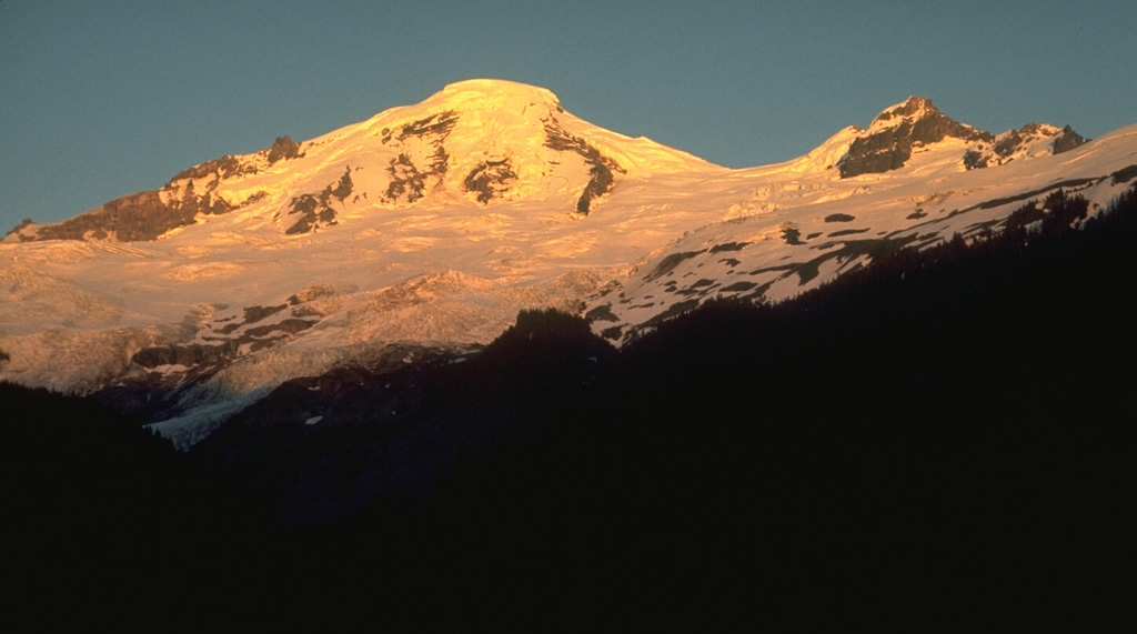 Mount Baker is seen here from the Glacier Creek valley on the NW side. Coleman Glacier is in the right-center of the photo with Coleman Saddle located between the summit and Colfax Peak on the right. The active Sherman Crater is on the opposite SE side of the summit. Photo by Lee Siebert, 1972 (Smithsonian Institution).