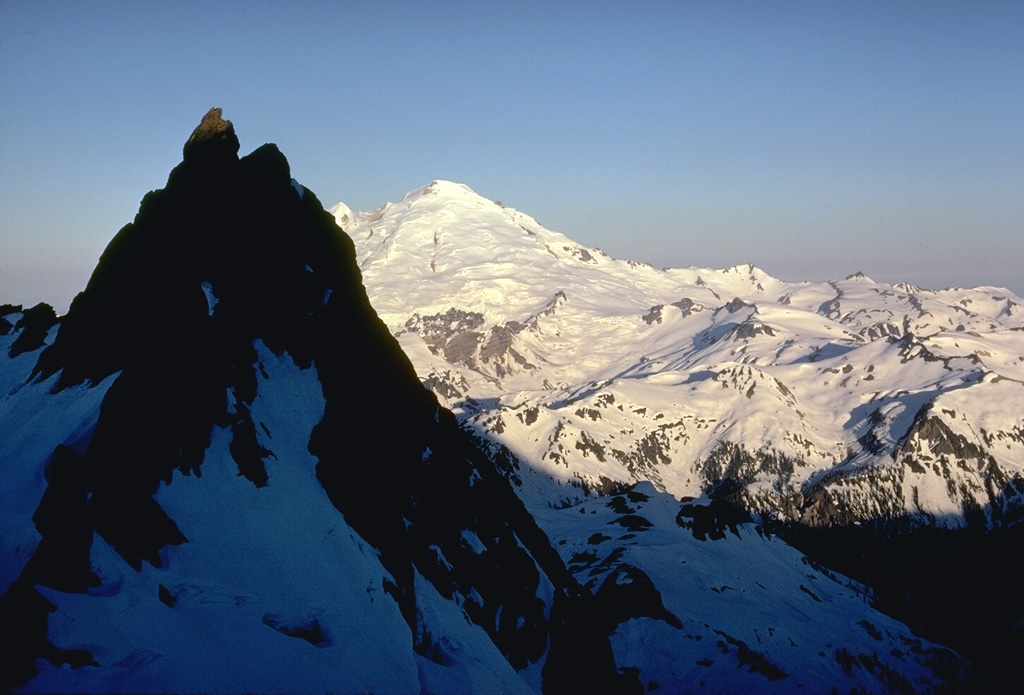 The glaciated surface of Mount Baker is seen here from neighboring Mount Shuksan. The peak in the shadow consists of metamorphosed basaltic rocks of the Shuksan Greenschist. The area to the right is the recently discovered Pleistocene Kulshan Caldera, which preceded the construction of Mount Baker. The 4.5 x 8 km caldera is largely filled by up to 1 km of non-welded tuffs and is capped by lava flows.  Photo by Lee Siebert, 1971 (Smithsonian Institution).