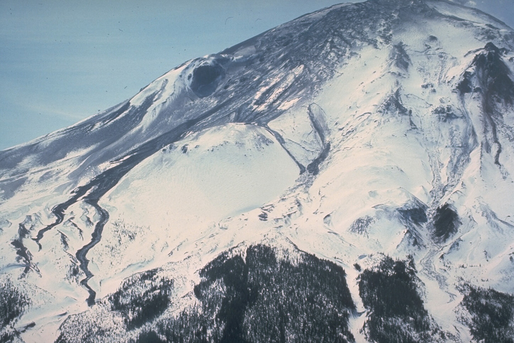 On 11 April 1980, two weeks after the 27 March beginning of the eruption of Mount St. Helens, an area of fractured glacial ice is visible at the top of the volcano. Thin black streaks of volcanic mudflows are visible at the center and lower left that diverge around the undisturbed snowpack on Sugar Bowl lava dome. Photo by William Melson, 1980 (Smithsonian Institution).