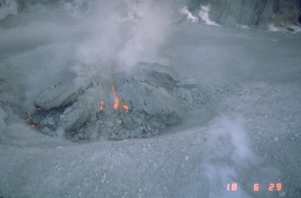 Incandescence is visible in fractures in a growing lava dome in the crater of Mount St. Helens on 18 October 1980. Several earlier lava domes that formed after 18 May 1980 had been removed by explosive eruptions. This photo shows the beginning stages of the lava dome that grew incrementally until the end of the eruption in October 1986. Photo by Terry Leighley, 1980 (U.S. Geological Survey).