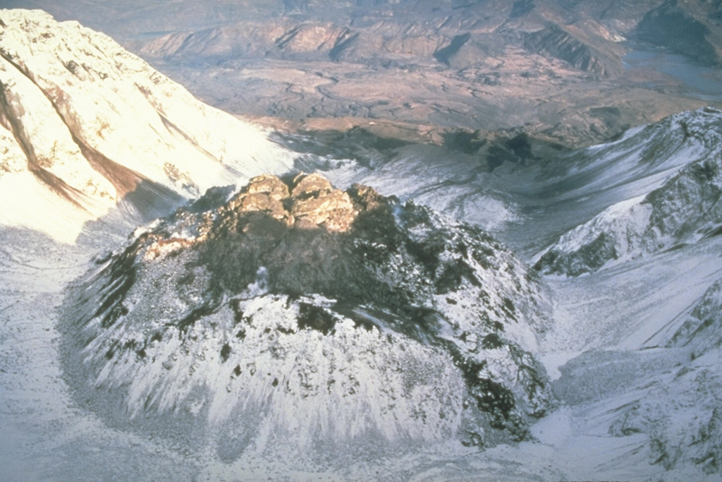 This view from above the south rim of the crater of Mount St. Helens shows the lava dome partially filling the crater on 28 October 1986, at the very end of the 1980-86 eruption. After six years of episodic growth the lava dome reached a height of 250 m and a diameter of 1,100 m. Photo by Lyn Topinka, 1986 (U.S. Geological Survey).