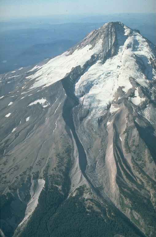 The north flank of Mount Hood is cut by the Eliot Glacier, with a series of prominent glacial moraines at its base.  During the past 1800 years eruptions of Mount Hood have been restricted to vents on the SW flank, resulting in proportionately more erosional dissection of the north flank of the volcano. Photo by Willie Scott, 1987 (U.S. Geological Survey).