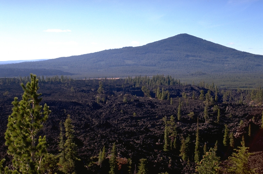 The middle of three flat-lying andesitic lava flows erupted from vents near Davis Lake has been radiocarbon dated at 4740 years.  The Pleistocene andesitic shield volcano Odell Butte is in the background, and the southernmost of the three lava flows can be seen in the distance below its left skyline. Photo by Lee Siebert, 1995 (Smithsonian Institution).