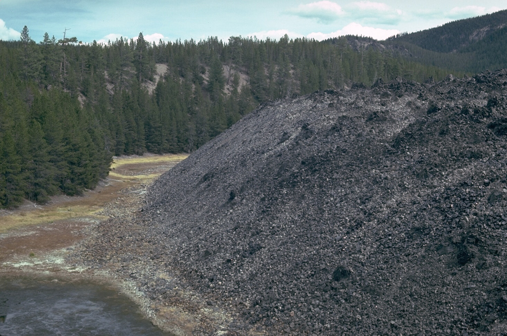 The NE margin of the Big Obsidian Flow, erupted from a vent near the south caldera wall of Newberry volcano about 1300 years ago, flowed into the crater of a pumice ring, whose forested rim is seen at the left and center.  The pumice ring formed during an earlier Holocene eruption about 6400 years ago. Photo by Lee Siebert, 1981 (Smithsonian Institution).