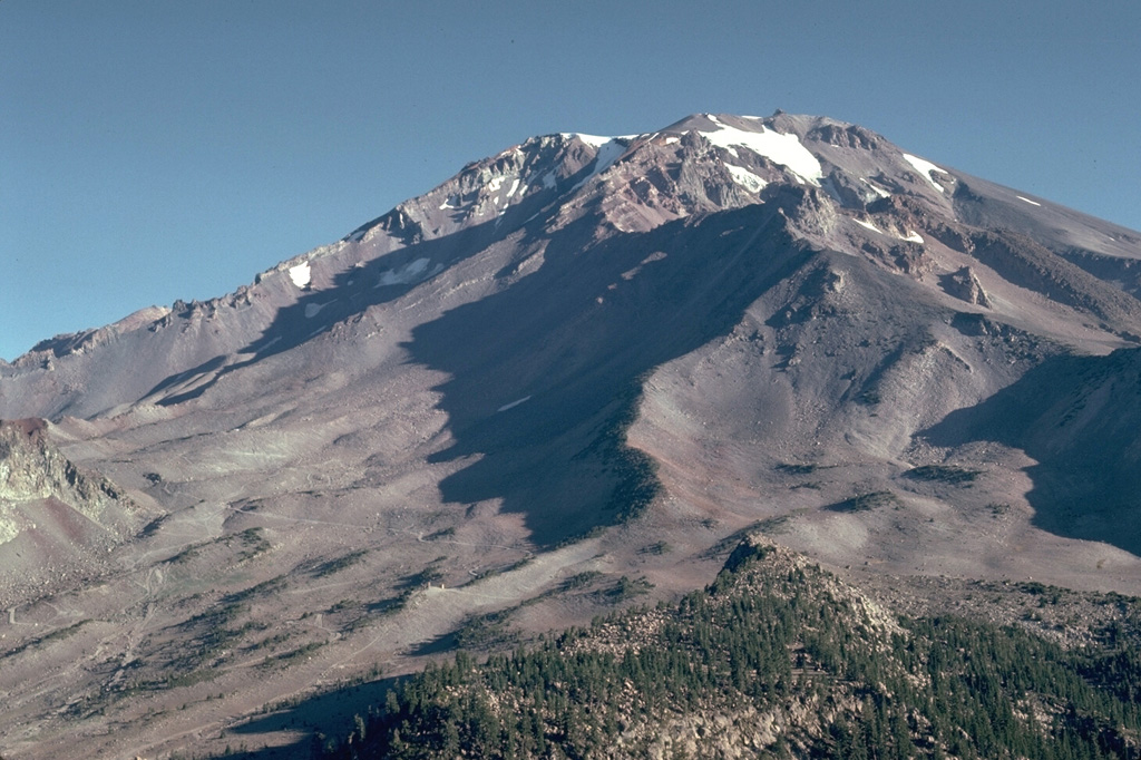 The extensively eroded Sargents Ridge (right center), on the south side of Mount Shasta, is the oldest of four major edifices that were constructed following the collapse of ancestral Mount Shasta.  The Sargents Ridge cone formed during the Pleistocene, less than 250,000 years ago.  Mount Misery, which forms much of the upper part of the cone and overlies the Sargents Ridge cone, formed less than 130,000 years ago. Photo by Lee Siebert, 1981 (Smithsonian Institution).