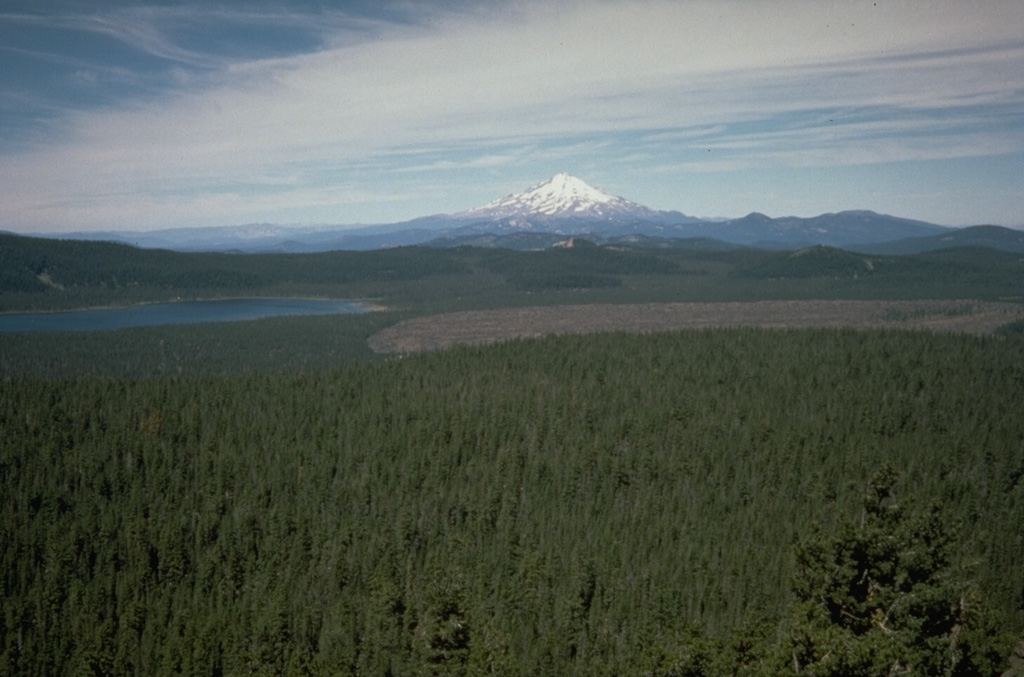 Medicine Lake volcano, seen here from the east with Mount Shasta in the background, is a massive, low shield volcano truncated by a 7 x 12 km summit caldera that is partially filled by Medicine Lake on the left.  The barren Medicine dacite flow on the right was erupted about 2000 years ago.  During the Holocene, obsidian flows have been erupted from summit and flank vents and voluminous basaltic lava flows have erupted from vents on the north and south flanks. Photo by Dan Dzurisin, 1985 (U.S. Geological Survey).
