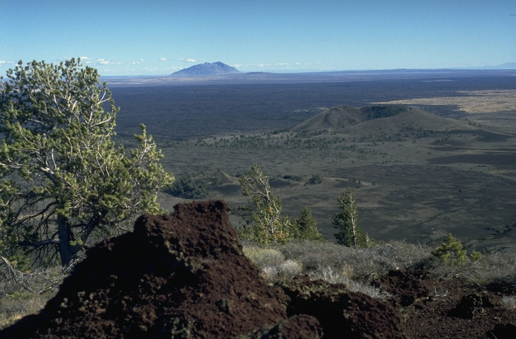 The vast extent of the Blue Dragon lava flow, forming the flat area in the middle of the photo, can be appreciated in this view from Big Cinder Butte with Big Southern Butte in the background to the east.  The Blue Dragon flow, the largest volume lava flow at Craters of the Moon, covers 280 sq km with 3.4 cu km of lava.  The flow was erupted about 2075 years ago and covers broad areas as far as 25 km to the east and 15 km to the SW of its vent area. Photo by Lee Siebert, 1994 (Smithsonian Institution).