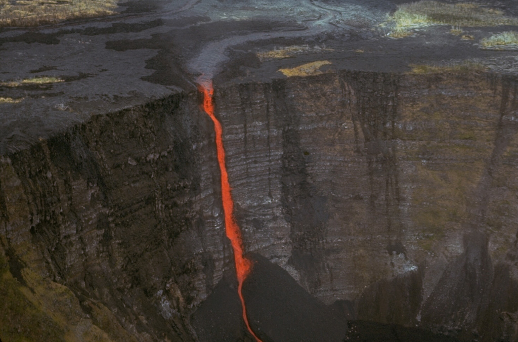 A stream of lava from a vent at Mauna Ulu (above the top of the photo) cascades into Makaopuhi crater during an early stage of the 1969-74 Mauna Ulu eruption. A thick stack of older lava flows that were erupted along Kilauea's East Rift Zone is exposed in the Makaopuhi crater wall.  Photo by Jim Moore (U.S. Geological Survey).