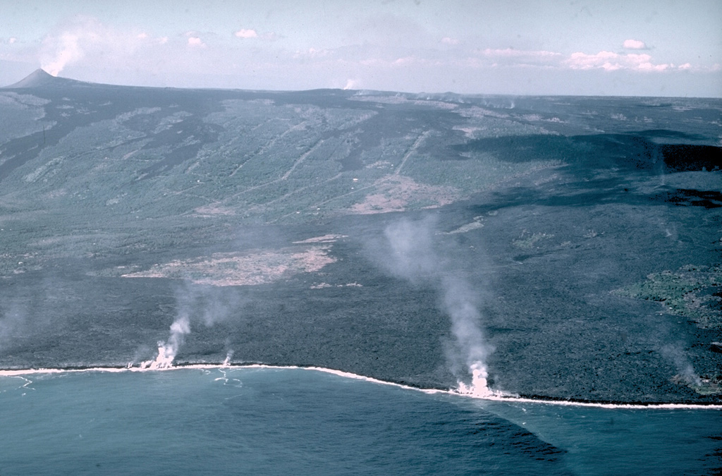 Laze (a plume of hydrochloric acid, steam, and fine glass particles) rises along the Puna coast where lava flows enter the sea in this 28 December 1987 photo. The flows originated from a fissure along Kilauea's East Rift Zone from the Pu'u 'Ō'ō scoria cone (upper left) to the Kūpaianaha lava lake (small gas plume in the center of the horizon). Lava flows traveled 10 km to the coast and inundated several subdivisions and villages.  Photo by J.D. Griggs, 1987 (U.S. Geological Survey).