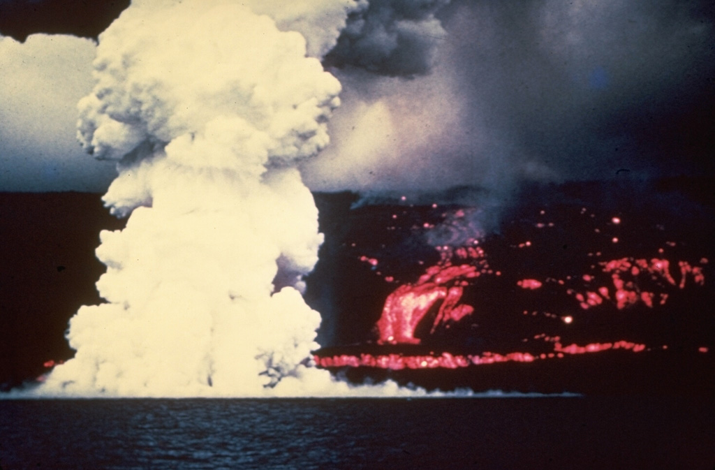 A laze plume (hydrochloric acid, steam, and fine glass particles) rises from the west coast of the Island of Hawai'i on 2 June 1950 where a lava flow from Mauna Loa enters the sea. The Ka'apuna lava flow (right) was the last of three lobes that entered the sea on the second day of an eruption that originated high on the SW rift zone. The lava flow crossed the road encircling the island near Heku Point and destroyed a new restaurant and several buildings. The eruption lasted until 23 June.  Photo by Gordon Macdonald (U.S. Geological Survey).