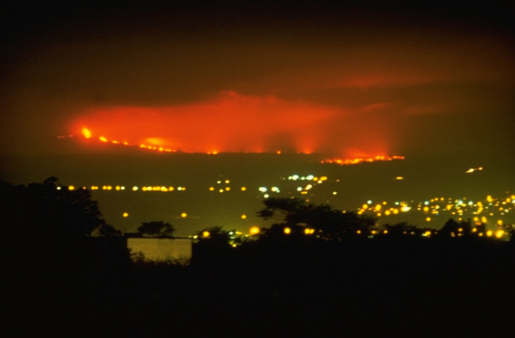 This nighttime view from the city of Hilo shows lava flows from Mauna Loa descending its NE flank on 4 April 1984. The flows traveled 42 km from vents on the upper NE rift zone of Mauna Loa, finally stopping only 5 km from the Hilo city limits. The 1984 lava flows were among the longest during historical time from Mauna Loa, matching the length of the 1942 flows. The 1855 and 1881 lava flows traveled significantly further; the latter reaching within 2 km of Hilo Bay.  Photo by David Little, 1984 (U.S. Geological Survey).