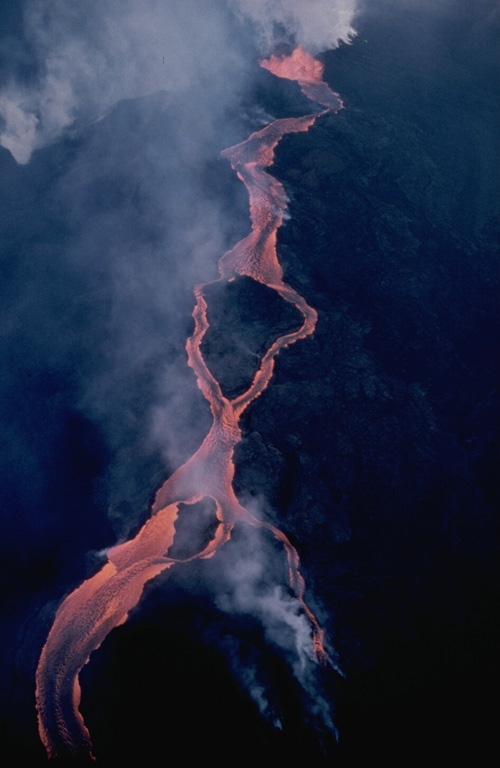 A lava flow from the Mauna Loa NE rift zone travels down the eastern flank on 30 March 1984. The flow developed a braided morphology as it moved around topographic highs. These flows originated from the easternmost vents of the 1984 fissure that opened during the afternoon of 5 March just below Pu'u 'Ula'ula; that remained the only active vent through to the end of the eruption on 15 April. Photo by J.D. Griggs, 1984 (U.S. Geological Survey).