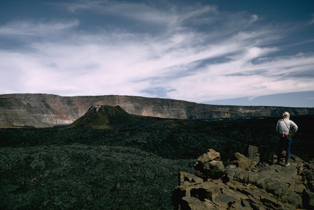 The spatter cone that formed during the 1940 eruption of Mauna Loa is seen in Moku'aweoweo caldera in this 1966 view from the southern rim of the caldera with the western caldera wall in the background. The eruption began along a 6-km-long fissure that extended across the caldera and down the SW rift zone. Activity soon became focused within the caldera and lava flows covered two-thirds of the caldera floor.  Photo by Richard Fiske, 1966 (Smithsonian Institution).