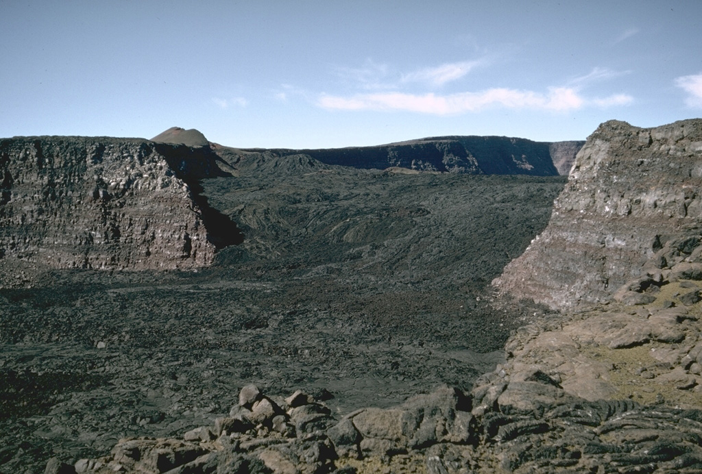This view looks across Mauna Loa's South Pit towards Moku'aweoweo caldera in 1966. The lava flows seen here erupted in 1949 within the caldera, then flowed into South Pit after covering the southern caldera floor and continued south for an additional 9 km beyond this crater. The small scoria cone on the horizon was constructed along the main fissure, which fed a lava flow that traveled 11 km down the west flank early in the eruption. Photo by Richard Fiske, 1966 (Smithsonian Institution).