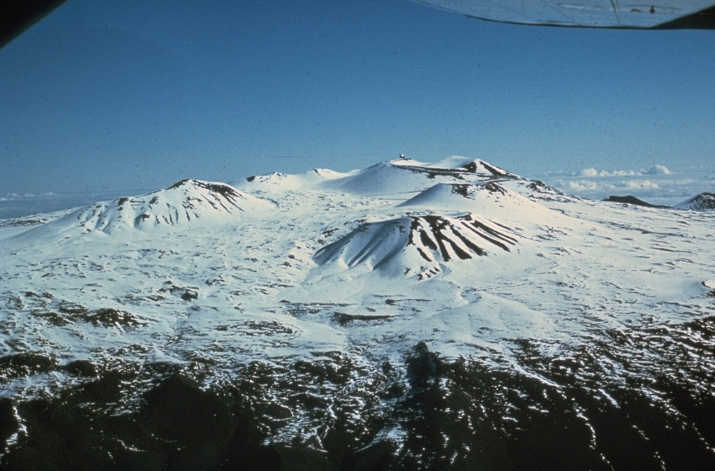 The snow-covered Mauna Kea summit exhibits scoria cones that formed late in the volcano's eruptive history, seen here from the SW. The high altitude makes it the only Hawaiian volcano that is known to have had glaciers.  Photo by Don Swanson (U.S. Geological Survey).