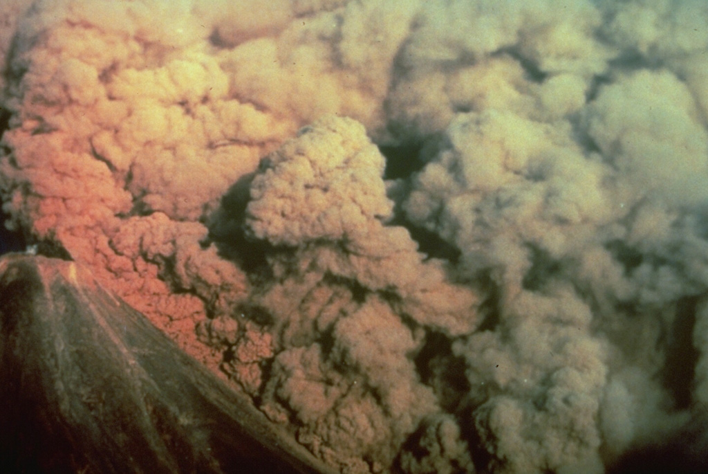 A convecting ash column rises above a small pyroclastic flow on the SW flank of Colima volcano in México on 16 April 1991. The pyroclastic flow, colored by the late-afternoon sun, was produced by the collapse of portions of the summit lava dome.  Photo by Alfredo Ramirez (pilot Ernesto Gómez Hofman), 1991 (courtesy Melchor Urzua, Protección Civil de Colima).