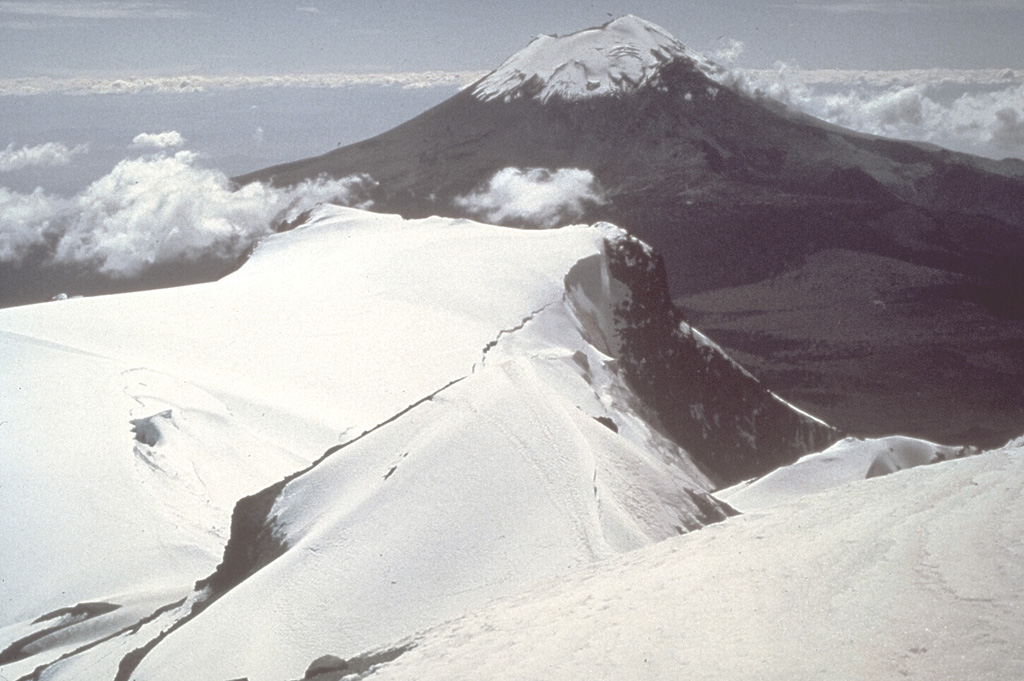 The symmetrical Popocatépetl volcano towers south of the elongated summit ridge of Iztaccíhuatl.  The two 5000-m-high volcanoes are popular climbing destinations from Mexico City, 60 km to the west.  Unlike the eroded Iztaccíhuatl volcano, which has been infrequently active during the Holocene, the conical Popocatépetl has been vigorously active. Photo by Jim Luhr, 1981 (Smithsonian Institution).