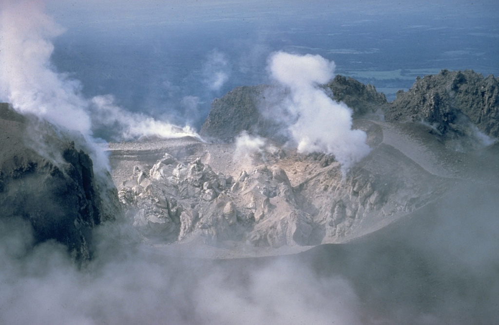 A blocky lava dome fills Caliente crater at the eastern end of the Santiaguito dome complex in June 1968.  Steam rises from fumaroles along the margins of the roughly 100-m-wide crater in this view from the north.  Periodic ash eruptions accompanied growth of the plug dome.  The Caliente vent is in the oldest part of the Santiaguito dome complex, which began growing in 1922.  It was the source of a major explosive eruption in 1929 that produced large pyroclastic flows. Copyrighted photo by Dick Stoiber, 1968 (Dartmouth College).