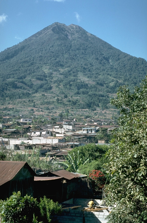 Agua volcano towers above the town of Santa María de Jesus on its NE flank.  The shallow summit crater of Agua is notched on its northern side and was the source of a major mudflow in 1541 that destroyed towns on the NW flank of the volcano.  This catastrophe was not accompanied by an eruption. Photo by Lee Siebert, 1988 (Smithsonian Institution).