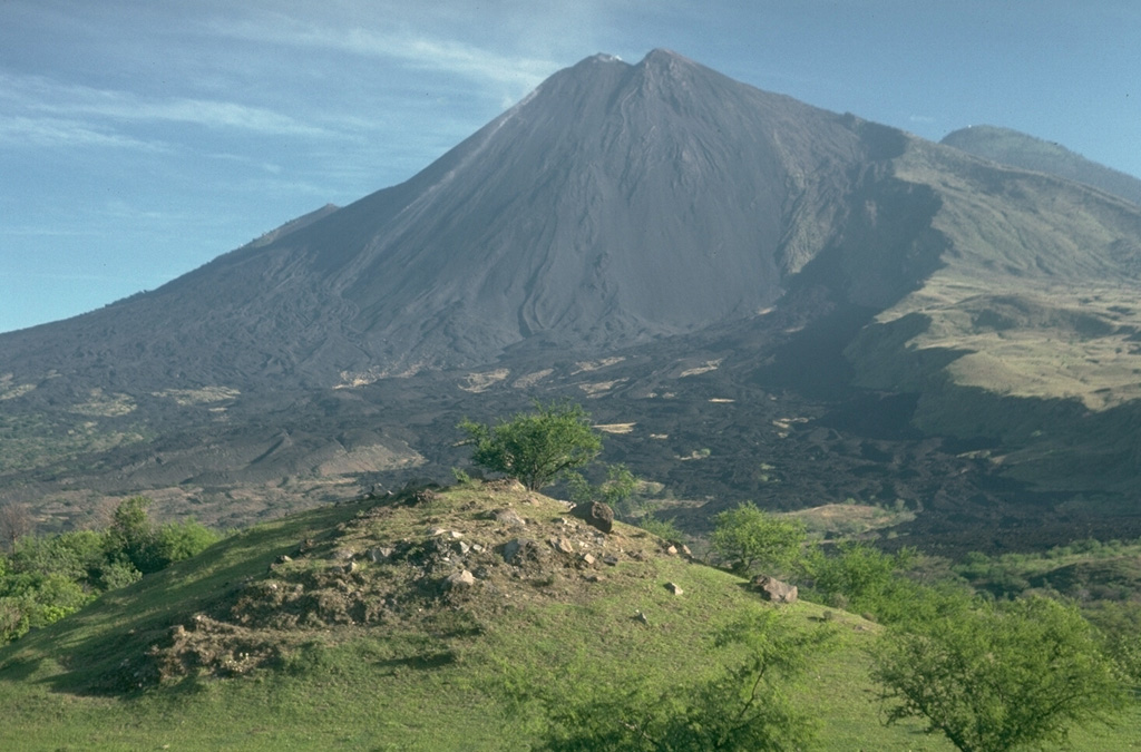 MacKenney cone, the historically active vent of Pacaya volcano in Guatemala, was constructed within a horseshoe-shaped crater produced by collapse of the summit of an ancestral volcano about 1,100 years ago. The SW crater rim forms the steep-sided scarp at the right. The blocky hill in the foreground is a hummock from the debris avalanche produced by the collapse. The avalanche extended for 25 km. Photo by Lee Siebert, 1988 (Smithsonian Institution).
