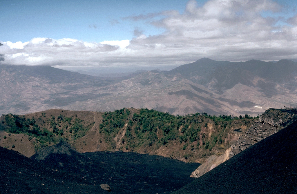 Cerro Chino, whose shallow crater rim can be seen at the left side of the long ridge cutting across the photo, was the site of a major eruption in 1775.  This eruption began at vents on the SW flank of Cerro Chino (behind the crater in this view) and then migrated towards the summit of Cerro Chino.  Powerful lava fountains were observed, and ashfall from this eruption, one of the largest in historical time at Pacaya, was reported up to 200 km away.  Fresh black lava flows in the foreground from MacKenney cone fill the moat between it and Pacaya's caldera rim. Photo by Lee Siebert, 1988 (Smithsonian Institution).