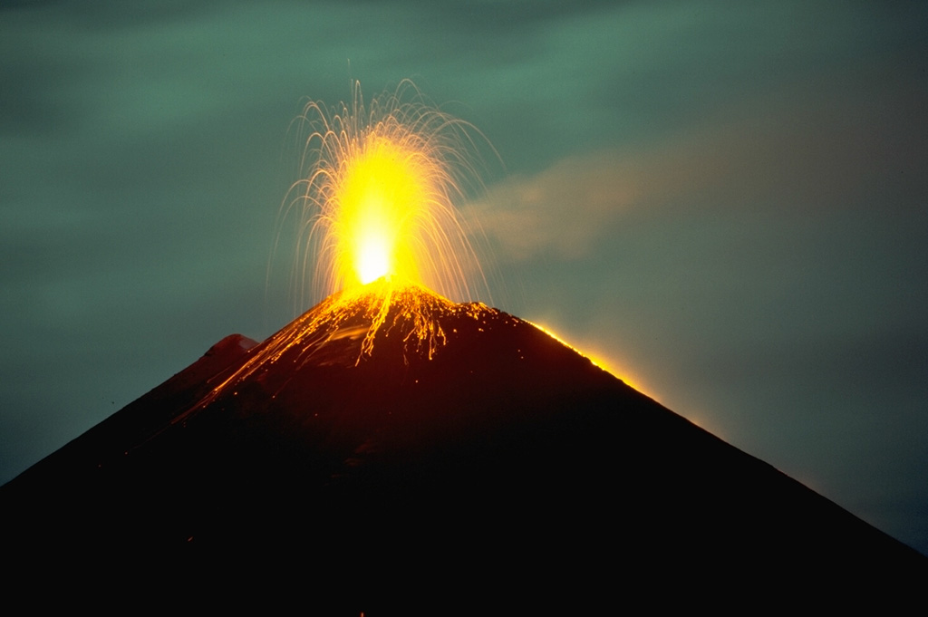 Long-term strombolian eruptions began at Pacaya volcano in 1965 and continued for more than a quarter century.  Nighttime incandescent explosions are often visible from Guatemala City, 40 km to the north.  The accumulation of ejecta from frequent strombolian eruptions periodically raises the height of MacKenney cone after it has been partially destroyed by intermittent larger explosions.  This November 1988 photo also shows a lava flow from a fissure on the west flank of MacKenney cone descending the right-hand skyline.  Photo by Lee Siebert, 1988 (Smithsonian Institution).