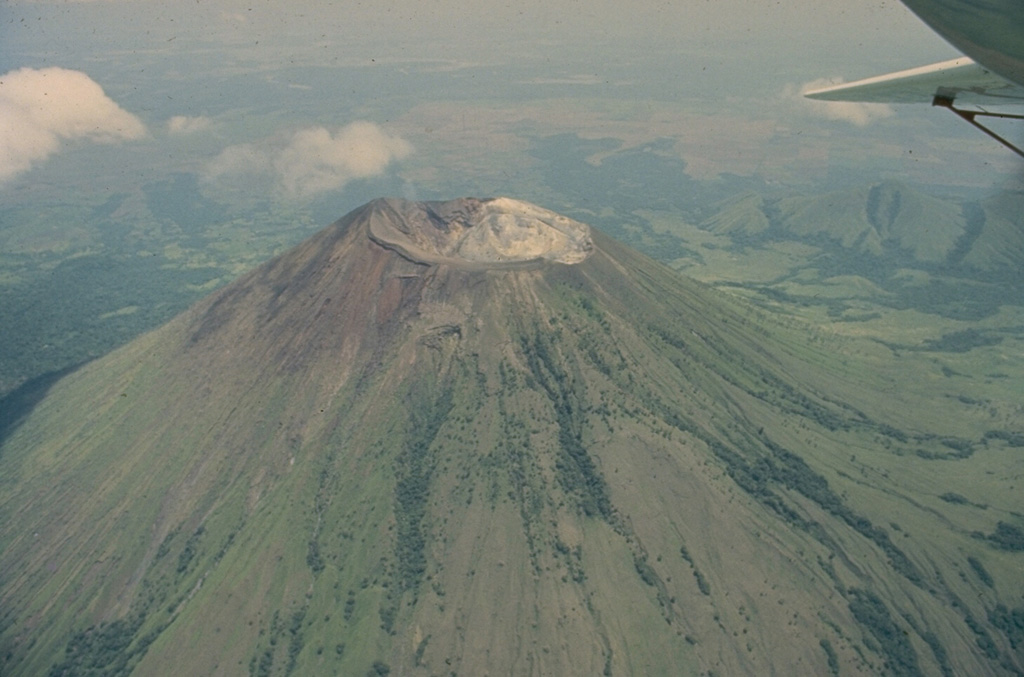 San Cristóbal, seen in this 1975 aerial view from the south, is the highest volcano in the Marrabios Range of western Nicaragua.  The symmetrical, 1745-m-high stratovolcano is the youngest of five principal volcanoes forming the San Cristóbal complex.  Young lava flows are located on its SW and northern flanks.  Explosive eruptions have occurred since the beginning of the Spanish era.  Cerro Moyotepe, a small composite volcano of the San Cristóbal complex that is cut by a series of N-S faults, appears at the right, below the plane wing. Photo by Jaime Incer, 1975.