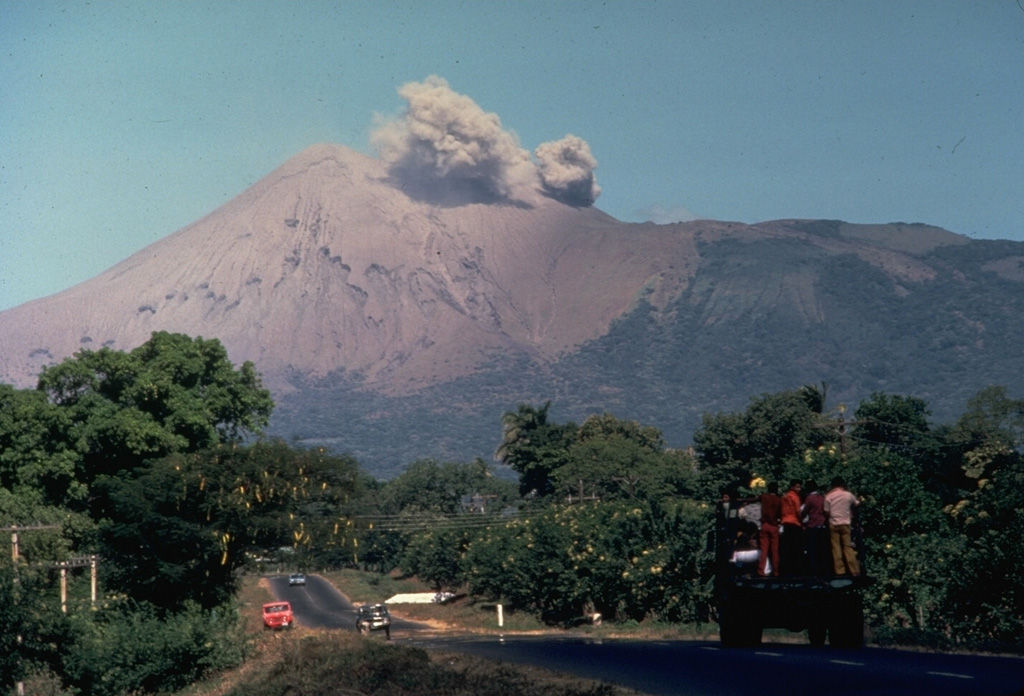 A small ash cloud from an eruption in 1977 rises from the crater of Telica volcano as seen from the outskirts of the city of León.  Intermittent explosions began in November 1976, and continued at a rate of one sizeable explosion a month until November 1977, when activity increased.  On November 11 ashfall reached the Pacific Ocean.  The eruption continued into January 1978. Photo by Jaime Incer, 1977.