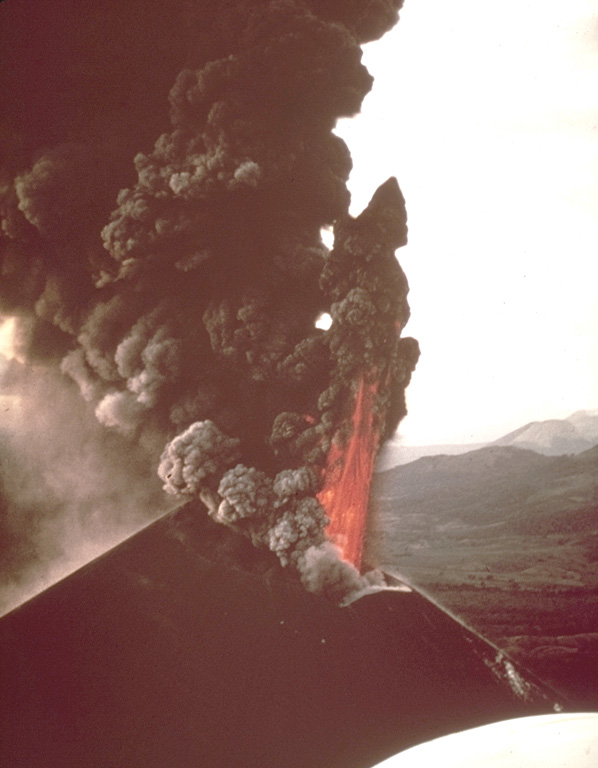An incandescent lava fountain and a thick ash-laden eruption column rise above the summit crater of Cerro Negro volcano in 1968.  Ash columns were distributed primarily to the west, and intense ashfall affected the León-Chinandega area, one of the most densely populated and important agricultural areas in Nicaragua.  This aerial view from the SE shows the Telica and San Cristóbal volcanic complexes in the far right distance.   Photo by William Melson, 1968 (Smithsonian Institution).