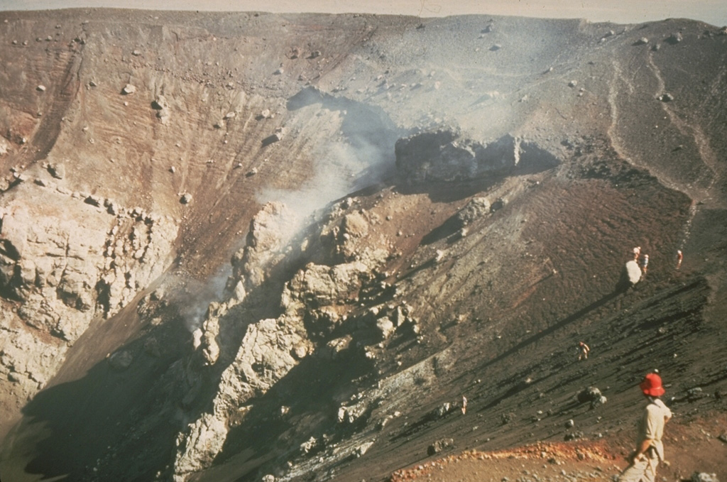 A geologist surveys the enlarged crater of Cerro Negro volcano in December 1972, observing the effects of the previous eruption during February 3-14, 1971.  Powerful explosions substantially enlarged the summit crater from 150 m in diameter before the eruption to 400 m after it.  This highly explosive eruption produced ashfall that caused extensive crop damage over a 5000 sq km area. Photo by Dennis Nielson, 1972 (courtesy of Mike Carr, Rutgers University).