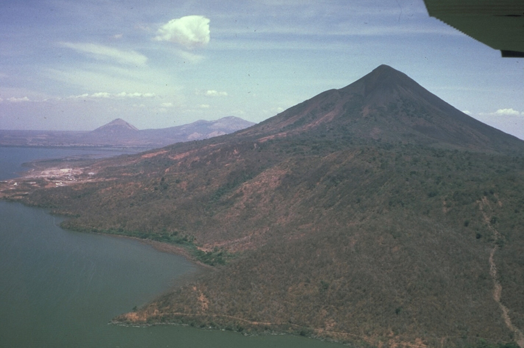 Momotombo volcano, seen here from the east, is a prominent youthful stratovolcano constructed along the shores of Lake Managua.  The peninsula in the foreground is Punta del Diablo, and the light-colored area at the left is the site of the Momotombo geothermal plant.  The young volcano is only 4500 years old and has a long record of strombolian eruptions, with occasional larger explosive activity.  In the distance are the conical peak of Cerro Asososca and the broad summit of Las Pilas volcano. Photo by Jaime Incer, 1983.