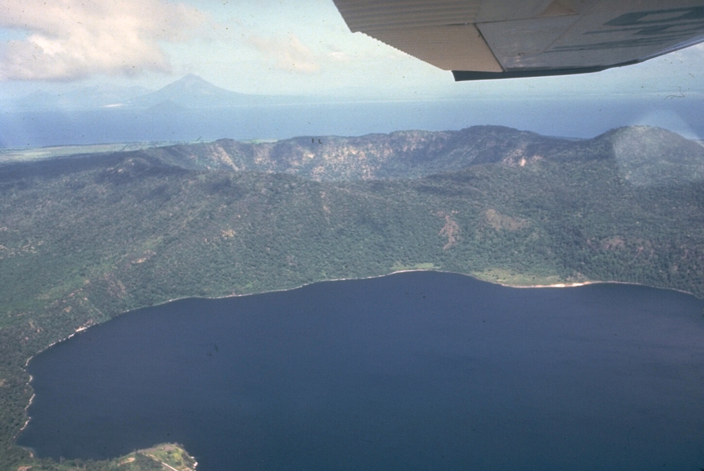 Apoyeque stratovolcano forms the large Chiltepe Peninsula in central Lake Managua.  A 2.8-km wide, 500-m-deep caldera truncates the volcano's summit, below and to the left of the airplane wing.  Laguna de Jiloa, the large lake in the foreground, lies immediately SE of Apoyeque.  The age of the latest eruption of Apoyeque is not known, but human footprints underlie pumice deposits thought to originate from Apoyeque volcano or a nearby vent beneath Lake Managua.  Momotombo volcano is visible in the distance to the NW across Lake Managua.       Photo by Jaime Incer, 1981.