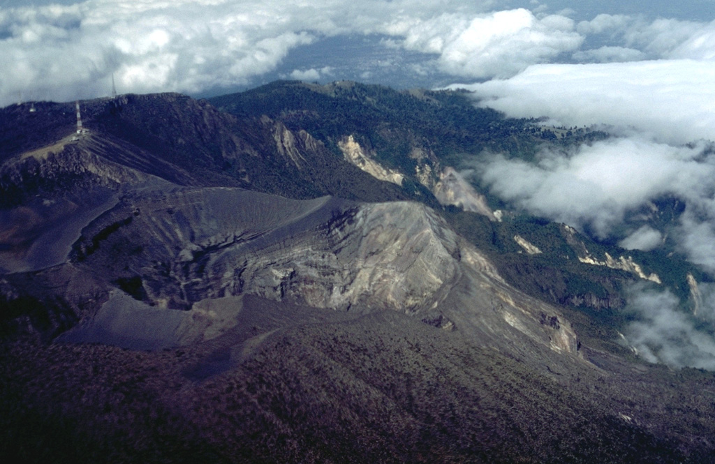 An aerial view from the east shows the active summit crater of Irazú at the left center.  This 600-m-wide crater has been the site of most of Irazú's historical eruptions.  At the lower left is the Diego de la Haya crater, last active during the 18th century.  The summit of the volcano is the centerpiece of Irazú National Park; forested valleys beyond the volcano are part of the Cordillera Volcánica Central Forest Reserve.  Communication towers occupy the summit of the volcano at the upper left. Photo by William Melson, 1986 (Smithsonian Institution).