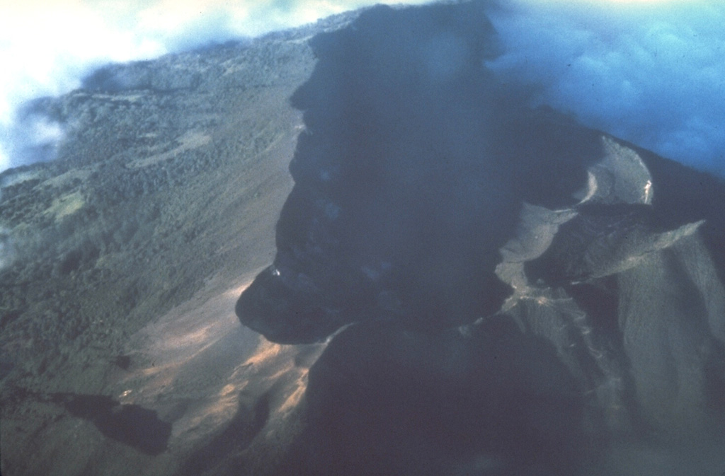 The summit crater complex of 3340-m-high Turrialba volcano appears in the shadow of this aerial view from the south.  Three overlapping craters, each of which contains sub-craters, occur within the 2 x 4 km summit depression.  A cloud bank at the upper right covers the breached NE end of the summit crater complex. Photo by Stan Williams (Arizona State University, courtesy of Mike Carr, Rutgers University).
