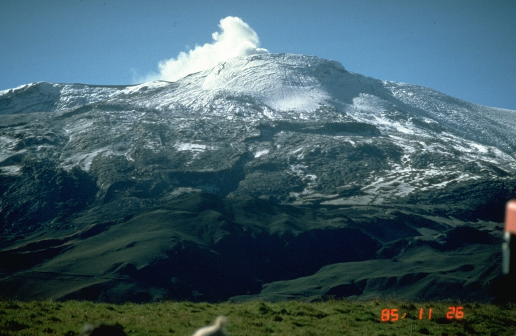 Two weeks after the November 13, 1985 eruption, steam rises from Las Arenas, the summit crater of Nevado del Ruiz.  This view from the NNW shows pyroclastic-surge and pyroclastic-flow deposits mantling the summit icecap.  Radial grooves descending the upper glacier surface were scoured by pyroclastic surges, which reached 5.5 km NW and NE of the summit.  Melting of the summit icecap led to the formation of devastating lahars that traveled as far as 100 km from the volcano and caused 23,000 fatalities. Photo by Norm Banks, 1985 (U.S. Geological Survey).