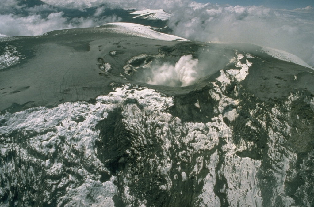 Steam rises from the summit crater of Nevado del Ruiz volcano on December 10, 1985.  Pyroclastic-surge and -fall deposits from the November 13 eruption extend from the crater.  Glaciers on the upper-NE-flank headwall of the Azufrado valley in the foreground were scoured by pyroclastic surges. Photo by Tom Pierson, 1985 (U.S. Geological Survey).
