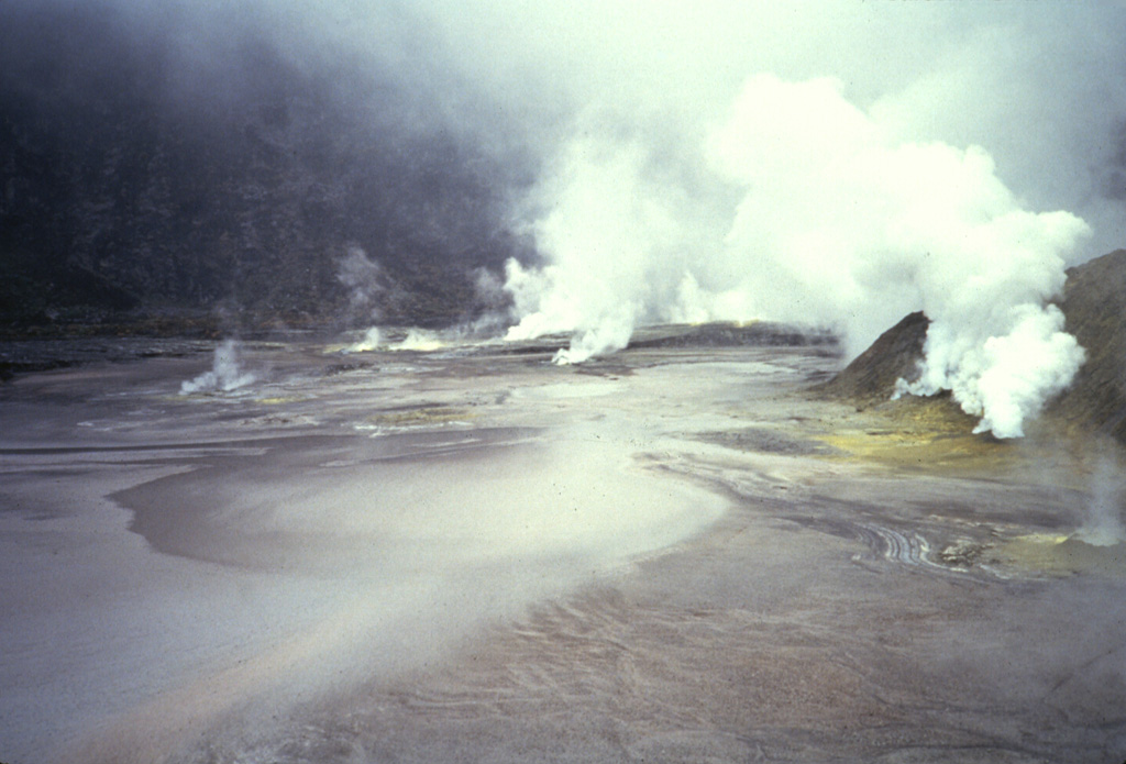 A dense plume emanates from fumaroles occupying the floor of Kaba Lama, the largest of the three major summit craters of Kaba volcano. A shallow lake occupying the crater floor is one of several in the Kaba crater complex. Anonymous, 1991.