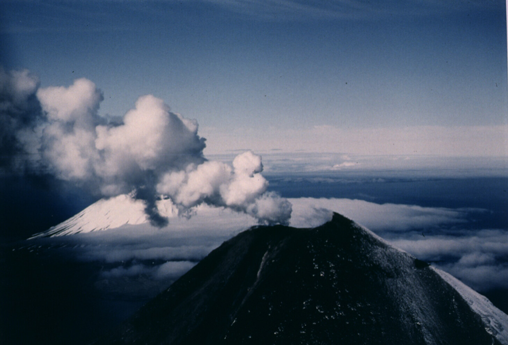 A gas-and-steam plume rises above the summit crater of Cleveland on 23 June 1987. The upper flanks are darkened by ashfall from an eruption that began on 19 June. A lava flow began on 23 June and eventually descended 2.5 km down the ESE flank. Lava fountaining was observed on 22 July. A large explosive eruption took place on 28 August, the last day of the eruption. This view from the ENE show part of Herbert volcano behind the plume to the left.  Photo by Harold Wilson, 1987 (Peninsula Airways), courtesy of John Reeder (Alaska Div. Geology Geophysical Surveys).