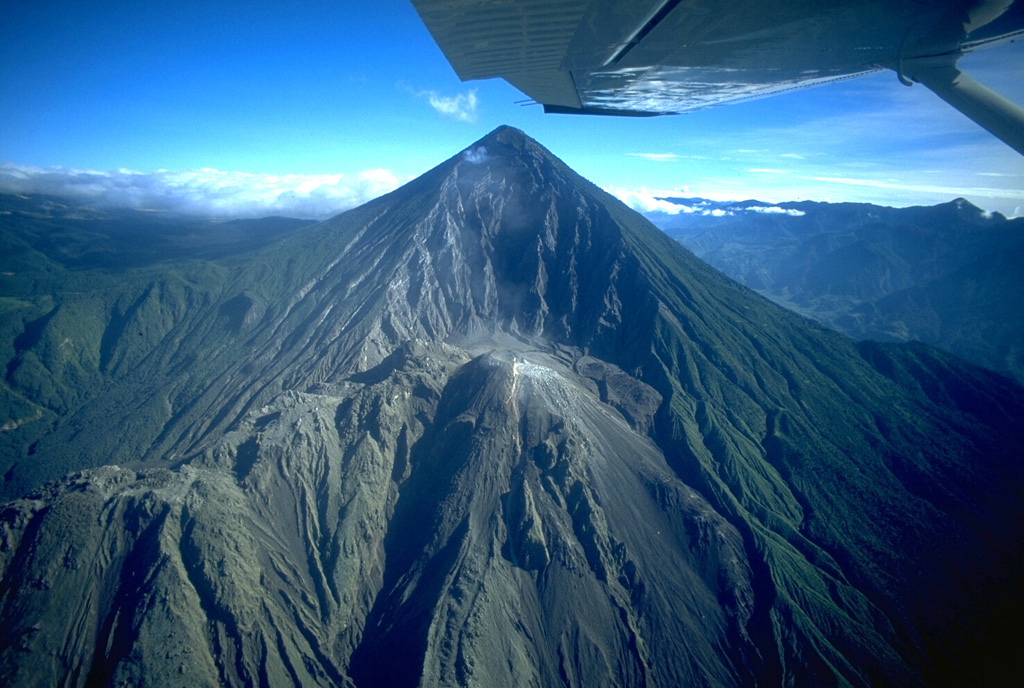 Santa María volcano, currently Guatemala's most active, is seen here in November 1994.  The upper SW flank of the 3772-m-high volcano is cut by a large 1-km-wide explosion crater formed during a catastrophic eruption in 1902.  Two decades later the Santiaguito lava dome began growing at the base of the crater, forming the elongated ridge seen below the summit and to the left.  Santiaguito has been continually active since 1922, with frequent explosive activity accompanying episodic periods of dome growth and lava extrusion. Copyrighted photo by Stephen O'Meara, 1994.