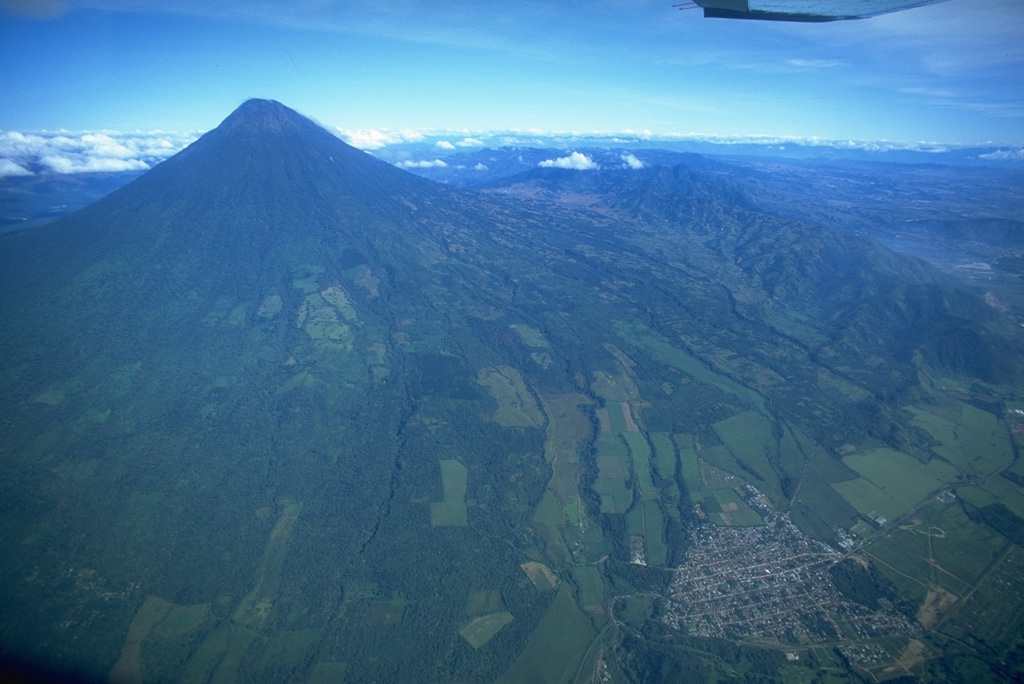 Symmetrical Volcán de Agua, seen here in an aerial view from the SE, is the easternmost of a chain of 3000-m-high conical stratovolcanoes rising above the Pacific coastal plain.  The town of Palín at the lower right lies along the highway between Guatemala City (just out of view to the right) and Escuintla.  No historical eruptions are known from Agua, which has the distinction of a soccer field in its small summit crater. Copyrighted photo by Stephen O'Meara, 1994.