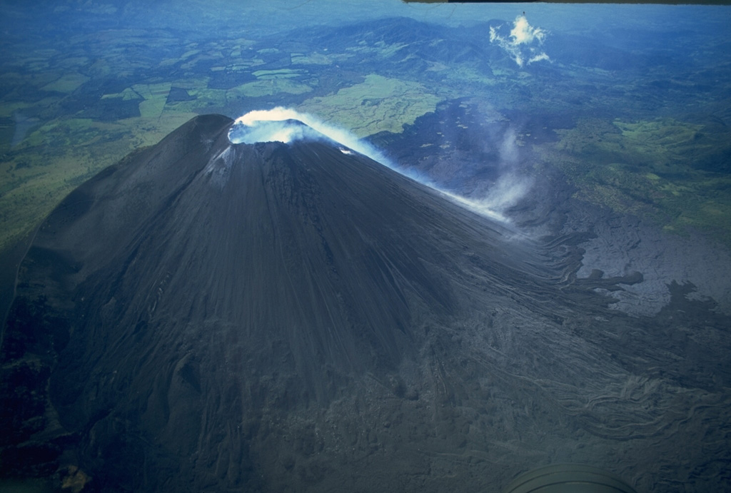 Steam pouring from the summit crater of MacKenney cone descends its SW flank in this November 10, 1994 aerial view of Pacaya.  After powerful explosions March 7-10, 1989 that destroyed the upper 75 m of MacKenney cone, strombolian eruptions resumed in early January 1990.  Explosive eruptions were accompanied by lava flows that again armored much of the cone. Copyrighted photo by Stephen O'Meara, 1994.