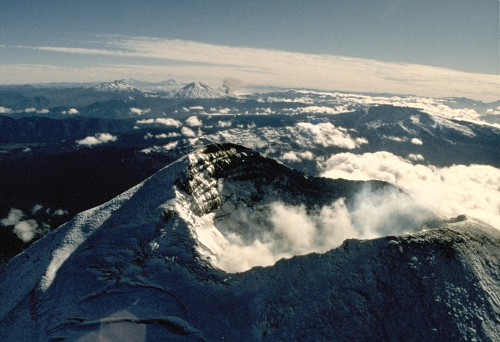 The summit crater of Llaima volcano appears in the foreground of this 1989 view looking north along the chain of Andean volcanoes.  An ash plume rises in the middle distance from a flank vent of Lonquimay volcano.  To its left is Tolguaca volcano, and Callaqui volcano lies farther to the north to the left of Lonquimay.  All these volcanoes except for Tolguaca have erupted in historical time; Llaima is one of Chile's most active volcanoes. Photo by Hugo Moreno, 1989 (University of Chile).
