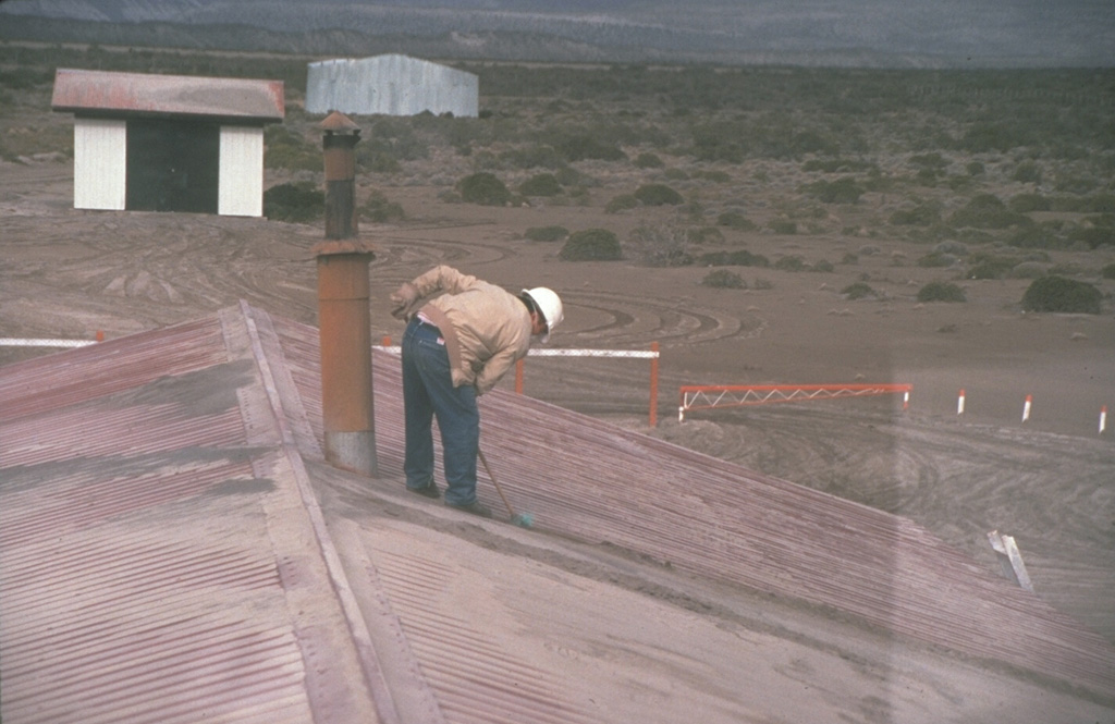 A resident of the Chilean town of Chile Chico, 125 km SE of Hudson volcano near the Argentinian border, sweeps ash from a rooftop on August 23, 1991.  One of the world's largest eruptions of the 20th century took place August 12-15, 1991.  It produced heavy ashfall across Argentina, damaging airport facilities and collapsing roofs of houses near the volcano.  Ash fell as far away as the Falkland Islands, 1000 km to the SE.  The fluorine-rich ash caused extensive mortality to grazing animals across Argentina. Photo by Norm Banks, 1991 (U.S. Geological Survey).