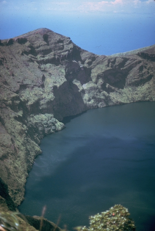 Prior to an eruption in 1971, the summit crater of Soufrière volcano was filled with a crater lake with a maximum depth of 180 m.  Its floor was 560 m below the north crater rim.  In 1971 a lava dome slowly and almost aseismically began growing on the crater floor.  It first breached the surface on November 3 and eventually formed a large island that left only a narrow moat of lake water. Photo by Jack Frost.