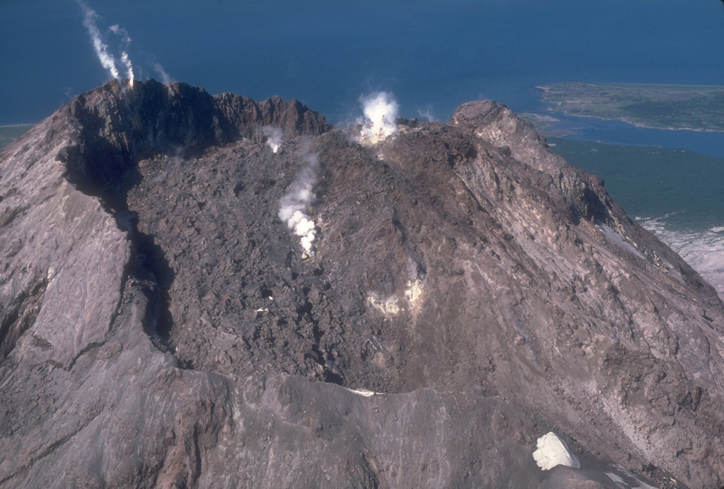 The 1976 lava dome, seen from the east in this 1982 photo of Augustine, is enclosed within an arcuate crater rim that was produced by explosive removal of part of the 1964 lava dome early during the 1976 eruption. The small peak to the upper right is a remnant of the 1935 lava dome. Small plumes rise from the 1976 dome (center) and from fumaroles at the summit of the 1964 dome remnant (upper left). Photo by Chris Nye, 1982 (Alaska Division of Geological and Geophysical Surveys).